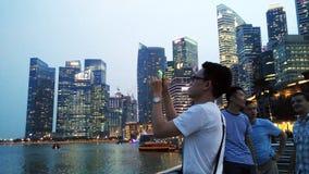 Photo de prise de touristes d'allumer Marina Bay Sands et le paysage urbain Photographie stock