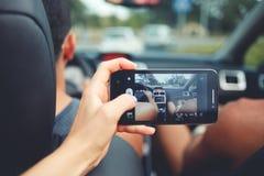 Photo de prise femelle avec l'appareil-photo de téléphone portable avec le véhicule pendant le voyage par la route Photos stock