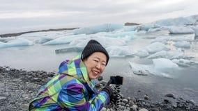 Photo de prise heureuse de dame âgée asiatique avec le lagoo de glacier de smartphone Photo libre de droits