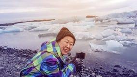 Photo de prise heureuse de dame âgée asiatique avec le lagoo de glacier de smartphone Images stock