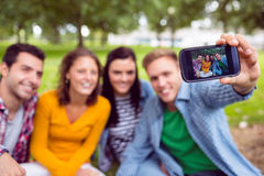 Photo de prise masculine avec des amis d'université en parc Images stock
