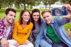 Photo de prise masculine avec des amis d'université en parc Photographie stock libre de droits
