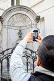 Photo de prise de touristes de Manneken Pis ou du petit pipi d'homme situé près de Grand Place dans la ville de Bruxelles, Belgiq Image stock