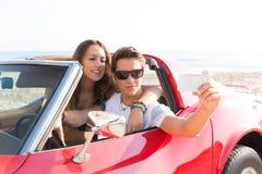 Photo de Selfie des couples de jeune adolescent dans le convertible Image stock