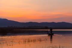 Photo de silhouette Le pêcheur sur le bateau le coucher du soleil Image stock