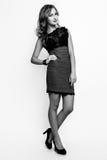 Photo de studio de jeune femme sur le fond blanc Noir et petit morceau Photo stock