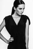 Photo de studio de jeune femme sur le fond blanc Noir et petit morceau Photos stock