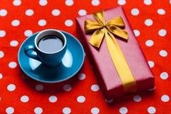 Photo de tasse bleue de café et de cadeau mignon sur le rouge pointillé de retour Images stock