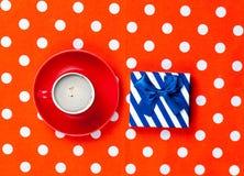 Photo de tasse de café et de cadeau mignon sur le rouge merveilleux pointillé Images stock