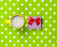 Photo de tasse de café et de cadeau mignon sur le vert merveilleux Photos libres de droits