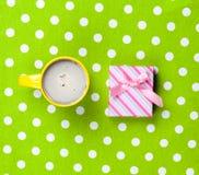 Photo de tasse de café et de cadeau mignon sur le vert merveilleux Photographie stock libre de droits