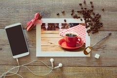 Photo de tasse de café sur la table en bois avec le téléphone et les grains de café futés Vue de ci-avant Photographie stock libre de droits