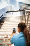 Photo de tir de personne de l'immeuble de bureaux avec le téléphone photos libres de droits