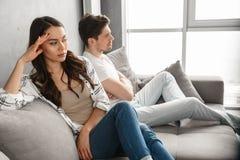 Photo de type irrité et de fille s'asseyant ensemble sur le divan au hom Images libres de droits