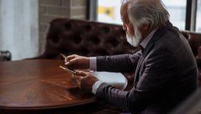 Photo de vieil homme tenant les verres et le smartphone sur les mains Images stock