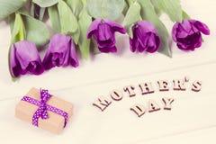 Photo de vintage, bouquet des tulipes pourpres et cadeau pour le jour du ` s de mère sur les conseils blancs Images libres de droits