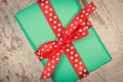 Photo de vintage, cadeau vert pour Noël ou toute autre célébration sur la planche en bois Photos stock