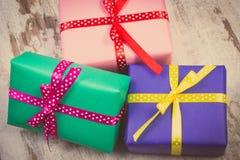 Photo de vintage, cadeaux colorés enveloppés pour Noël ou toute autre célébration sur la vieille planche blanche Photo libre de droits