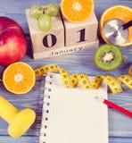 Photo de vintage, calendrier de cube, fruits, haltères et ruban métrique, nouvelles années de résolutions Photographie stock
