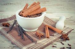 Photo de vintage, clous de girofle parfumés et cannelle en mortier et épices sur le conseil rustique Image stock