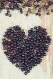 Photo de vintage, coeur de baie de sureau fraîche sur le vieux fond en bois, symbole de l'amour Photographie stock