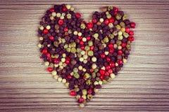 Photo de vintage, coeur de poivre coloré frais sur le fond en bois Photo libre de droits