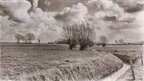 Photo de vintage d'un petit canal fonctionnant par un paysage avec des arbres photos stock