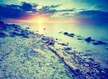 Photo de vintage du beau bord de mer rocheux au lever de soleil Photos stock
