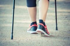 Photo de vintage, jambes du nordic de pratique de femme supérieure pluse âgé marchant, modes de vie sportifs dans la vieillesse Image stock
