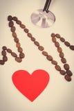 Photo de vintage, ligne de cardiogramme des graines de café, coeur rouge et concept de stéthoscope, de médecine et de soins de sa Image stock