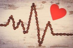 Photo de vintage, ligne de cardiogramme des graines de café rôties et concept rouge de coeur, de médecine et de soins de santé Photos stock