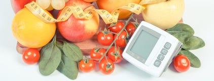 Photo de vintage, moniteur de tension artérielle, fruits avec des légumes et centimètre, mode de vie sain Image libre de droits
