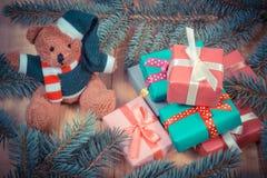 Photo de vintage, ours de nounours avec les cadeaux colorés pour Noël et branches impeccables Image libre de droits