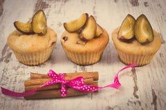 Photo de vintage, petits pains cuits au four frais avec des prunes et bâtons de cannelle sur le vieux fond en bois, dessert délic Images libres de droits