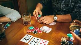 Photo de vue de côté des amis s'asseyant à la table en bois Amis ayant l'amusement tout en jouant le jeu de société Images libres de droits