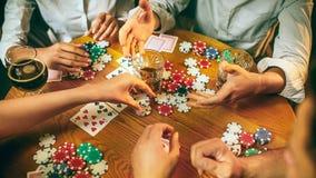 Photo de vue de côté des amis s'asseyant à la table en bois Amis ayant l'amusement tout en jouant le jeu de société Photo libre de droits