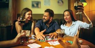 Photo de vue de côté des amis s'asseyant à la table en bois Amis ayant l'amusement tout en jouant le jeu de société Images stock