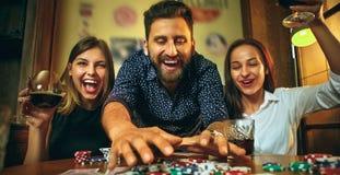 Photo de vue de côté des amis s'asseyant à la table en bois Amis ayant l'amusement tout en jouant le jeu de société Photos libres de droits