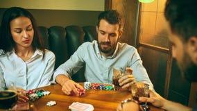 Photo de vue de côté des amis s'asseyant à la table en bois Amis ayant l'amusement tout en jouant le jeu de société Image stock