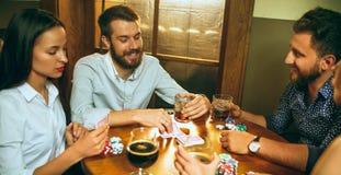 Photo de vue de côté des amis s'asseyant à la table en bois Amis ayant l'amusement tout en jouant le jeu de société Photos stock