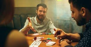 Photo de vue de côté des amis s'asseyant à la table en bois Amis ayant l'amusement tout en jouant le jeu de société Photographie stock