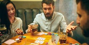 Photo de vue de côté des amis s'asseyant à la table en bois Amis ayant l'amusement tout en jouant le jeu de société Image libre de droits