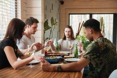 Photo de vue de côté d'un groupe d'amis priant au-dessus de la table de dîner Photos stock