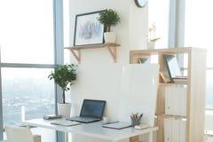 Photo de vue de côté de lieu de travail de studio avec le carnet vide, ordinateur portable Table de travail confortable de concep Photos libres de droits