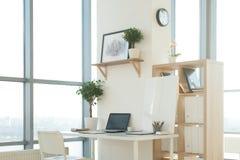 Photo de vue de côté de lieu de travail de studio avec le carnet vide, ordinateur portable Table de travail confortable de concep Photos stock