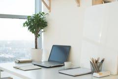 Photo de vue de côté de lieu de travail de studio avec le carnet vide, ordinateur portable Table de travail confortable de concep Photo libre de droits