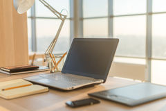 Photo de vue de côté de lieu de travail de studio avec le carnet vide, ordinateur portable Table de travail confortable, siège so Photo libre de droits
