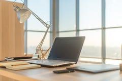 Photo de vue de côté de lieu de travail de studio avec le carnet vide, ordinateur portable Table de travail confortable, siège so Photos stock