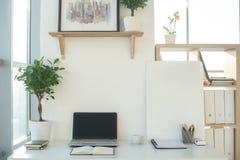 Photo de vue de face de lieu de travail de studio avec le carnet vide, ordinateur portable Table de travail confortable de concep Image libre de droits