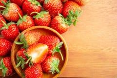 Photo de vue sup?rieure, un tas de la baie fra?che, fraise rouge sur le plancher en bois avec l'espace coppy photo stock